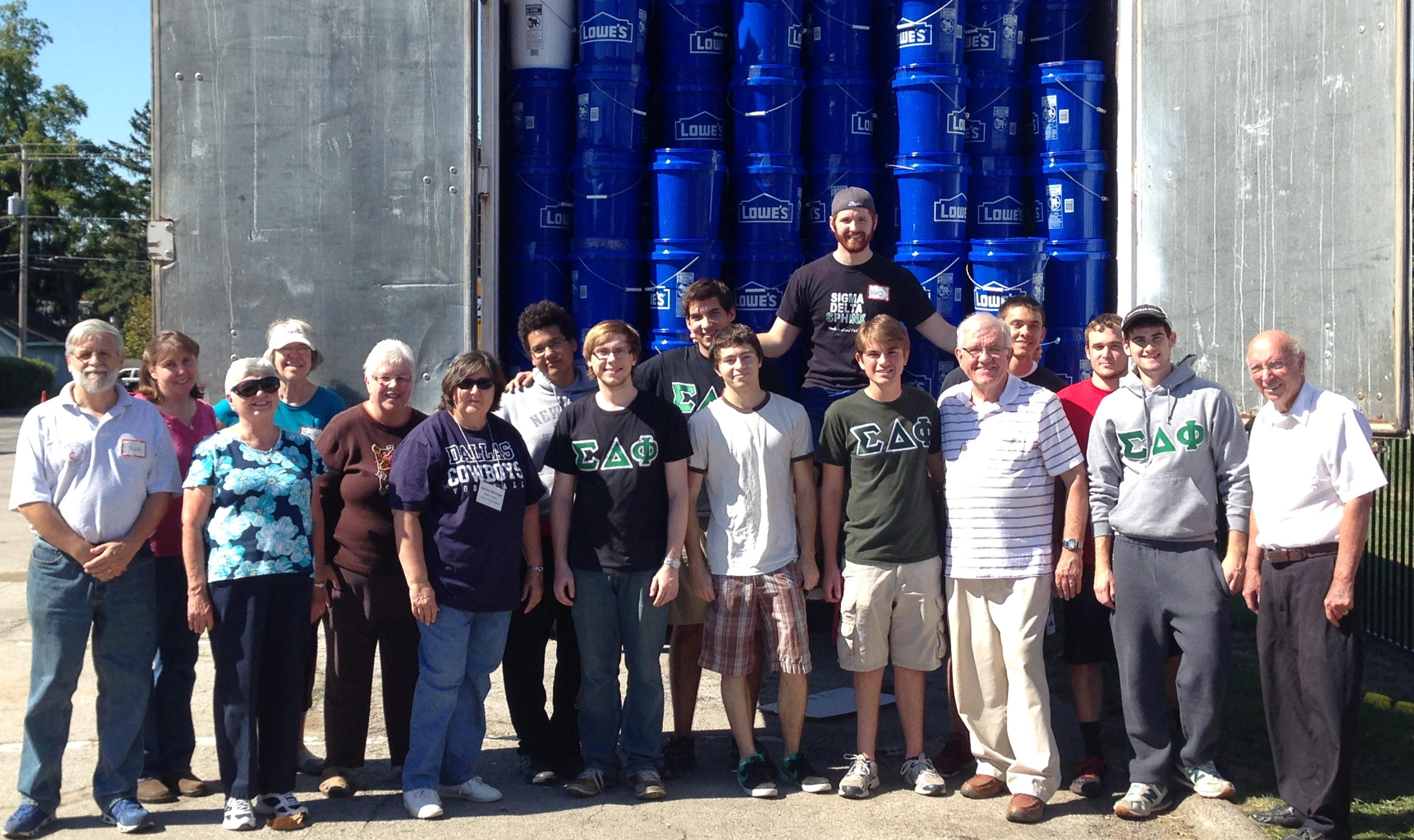 A group of volunteers standing in front of a truck, fully loaded with kits.